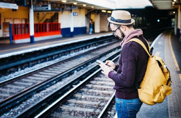 chico con el smartphone en una estación de tren